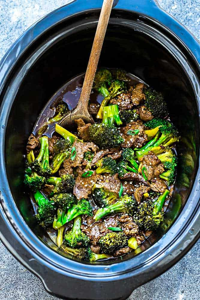 slow cooker beef and broccoli being stirred with a wooden spoon