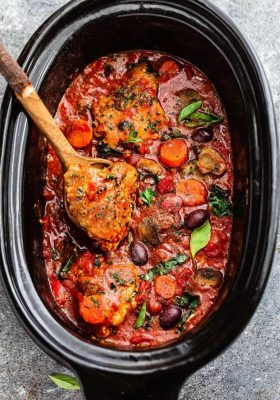 Slow Cooker Chicken Cacciatore being stirred with a wooden spoon