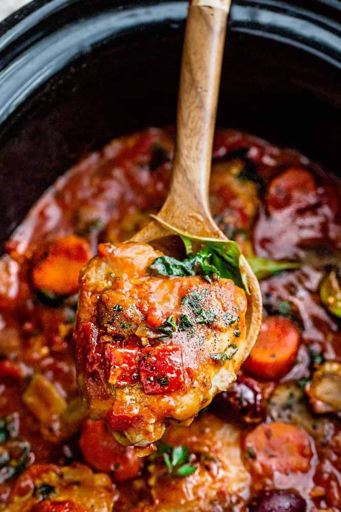 wooden spoon holding a serving of chicken cacciatore in a slow cooker