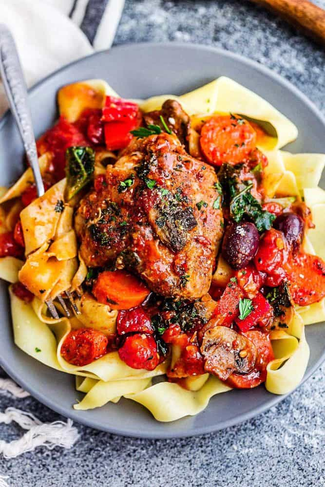 Dinner plate of slow cooker chicken cacciatore served over thick egg noodles