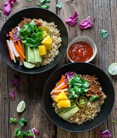 Top view of two Slow Cooker Honey Sriracha Pulled Pork Quinoa Bowls with colorful vegetables