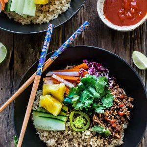 Top view of two Slow Cooker Honey Sriracha Pulled Pork Quinoa Bowls with colorful vegetables and a bowl of Sriracha sauce