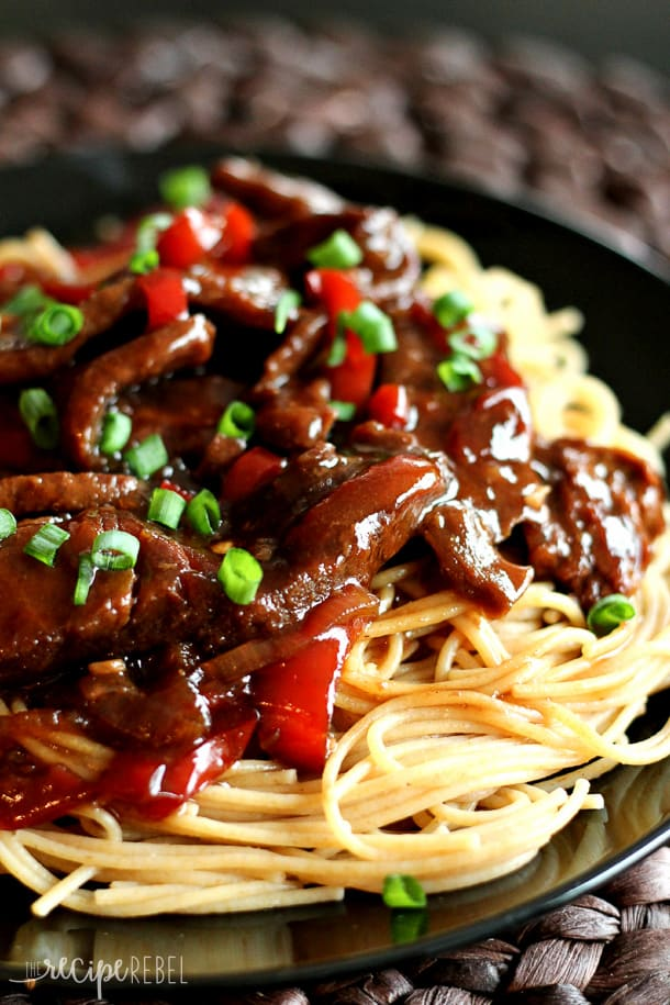 Slow cooker Mongolian Beef over spaghetti on a plate