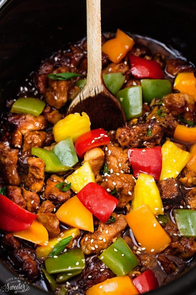 Sweet and Sour Chicken with pineapple in a slow cooker being stirred with a wooden spoon