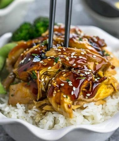Slow Cooker Teriyaki Chicken coated in a homemade sweet and savory Teriyaki sauce on a bed of white rice in a white bowl with chopsticks.