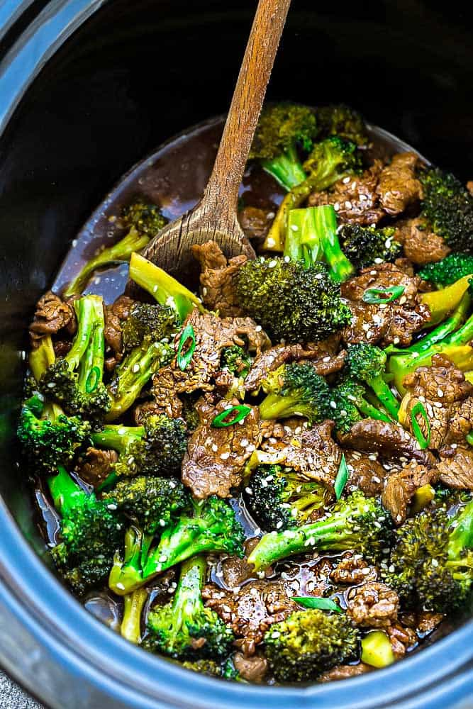 wooden spoon stirring a crock pot full of Asian beef and broccoli