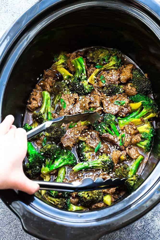 serving tongs in a slow cooker full of beef and broccoli