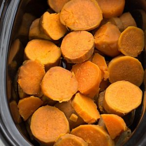 Top view of cooked sweet potato rounds in a slow cooker