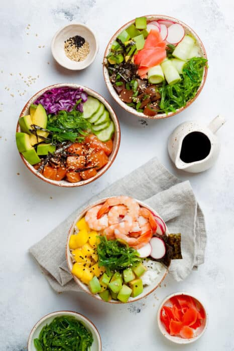 Top view of Hawaiian salmon, tuna and shrimp poke bowls with seaweed, avocado, mango, pickled ginger, sesame seeds.