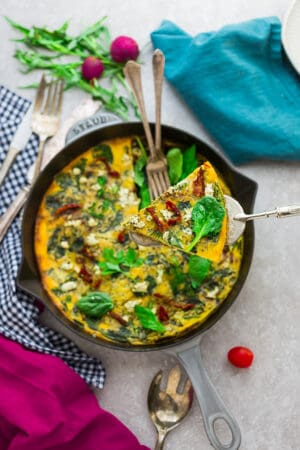Top view of Spinach Frittata with Sun-Dried Tomatoes in a Grey Cast Iron Skillet Pan with a missing slice and two forks