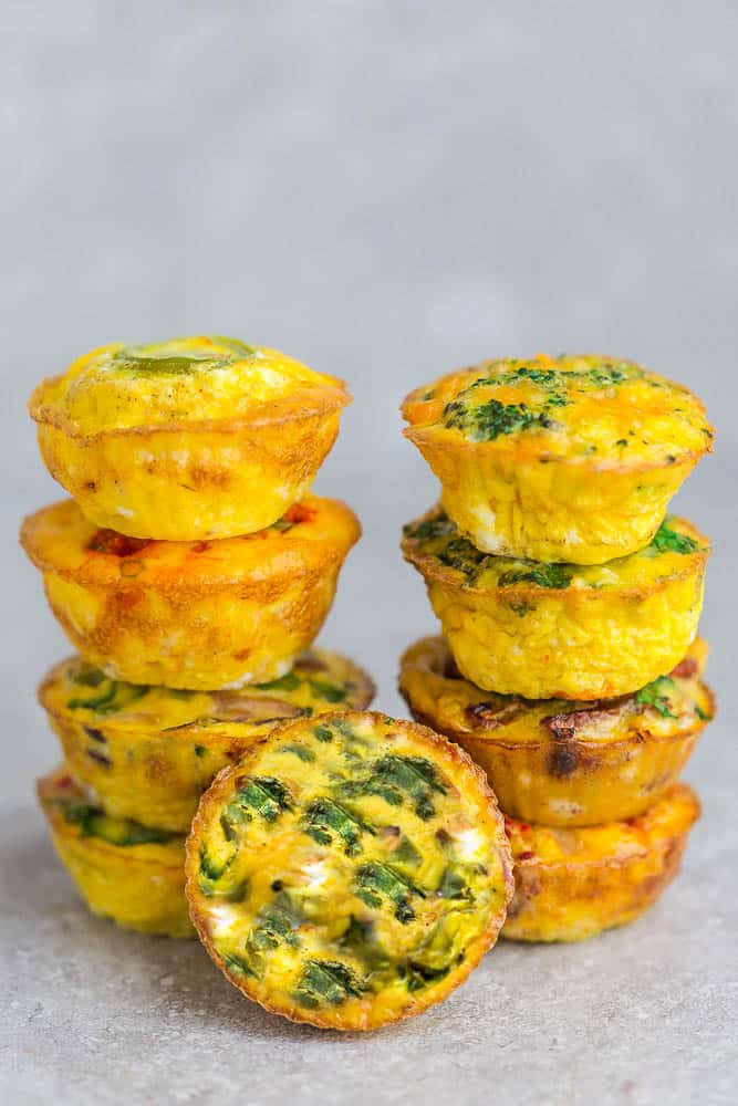 Side view of 9 spinach egg muffins stacked on a grey background