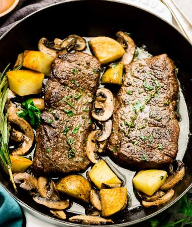 Top view of steak and Potatoes in a white cast iron pan