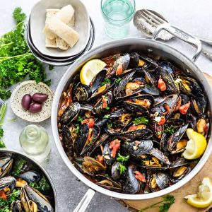 Top view of a serving bowl of Mediterranean Mussels with lemon wedges and olives
