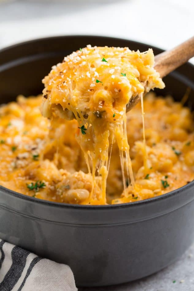 Side view of cheesy macaroni and cheese on top of wooden spoon.