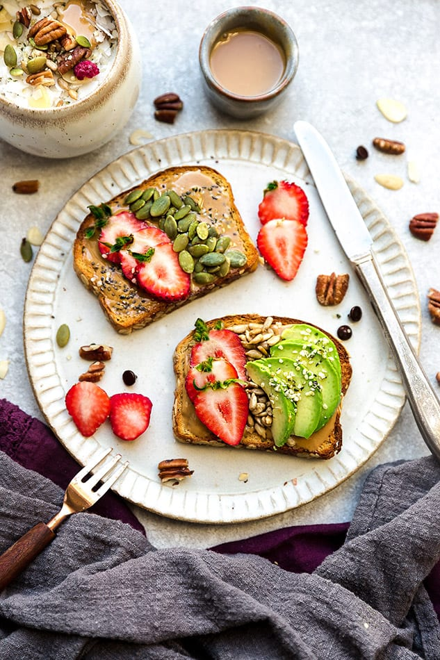 Top view of 2 slices of toast with avocado and strawberries on a white plate