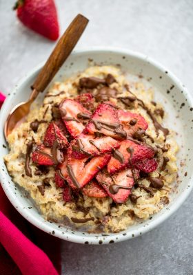 Top view of strawberry oatmeal in a white speckled bowl with a spoon on a grey background and a red napkin