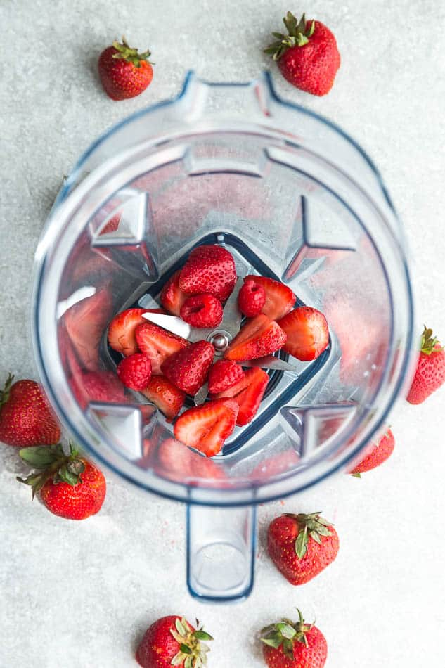 Top view of fresh strawberries and rasperries in a Vitamix blender on a grey background