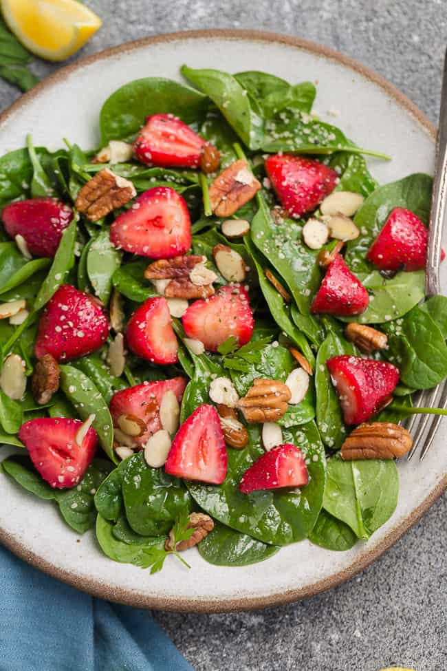 Top view of Whole30 strawberry spinach salad in a white bowl on a grey background