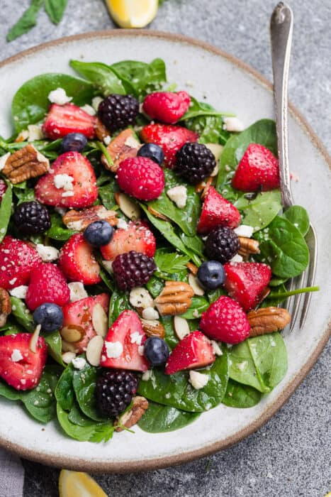 Top view of paleo strawberry spinach salad in a white bowl on a grey background