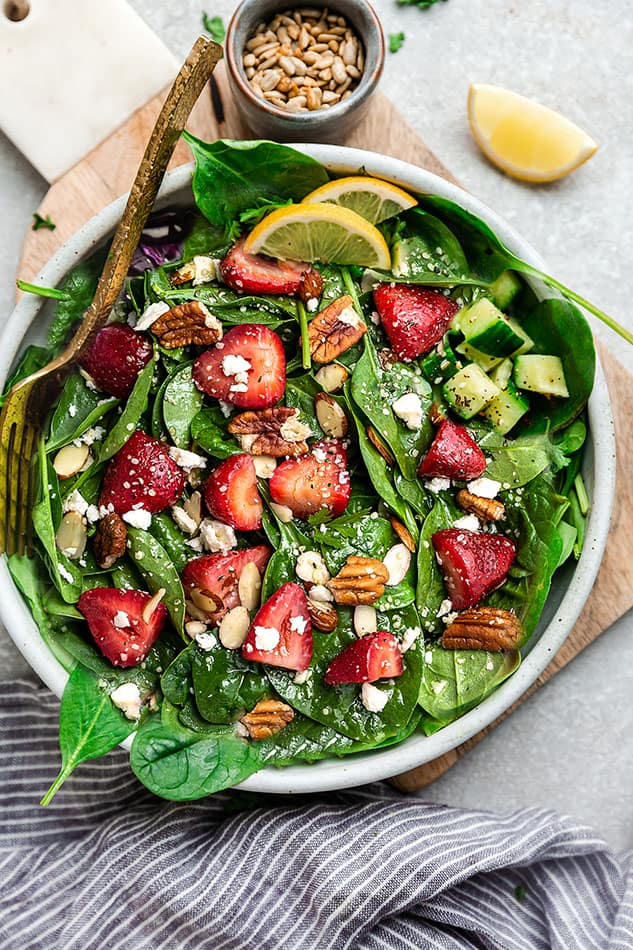 Top view of keto strawberry spinach salad in a white bowl on a grey background for berry recipes.