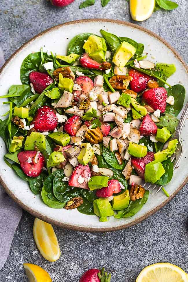 Close-up top view of healthy strawberry spinach salad in a white bowl on a grey background