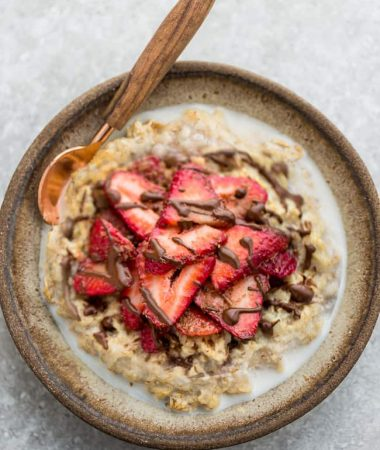 Top view of strawberry steel cut oats in a white speckled bowl with a spoon on a grey background and a red napkin