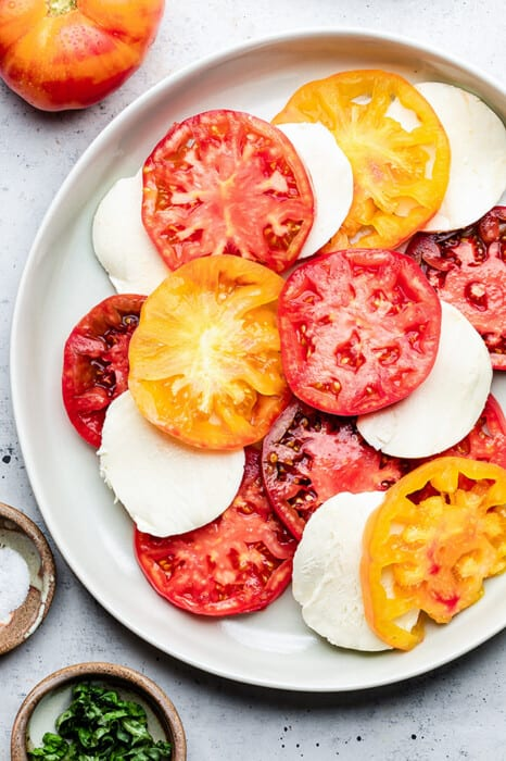 A white bowl of sliced heirloom tomatoes and mozzarella slices