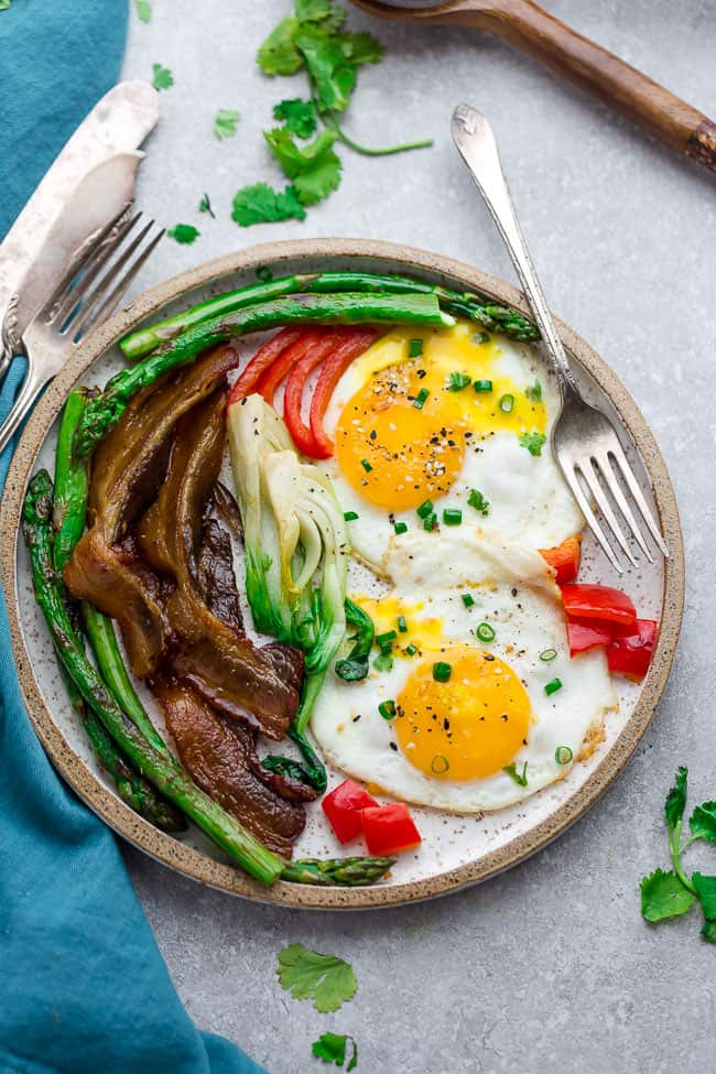 Top view of Sunny Side Up Eggs with bacon and vegetables on a plate