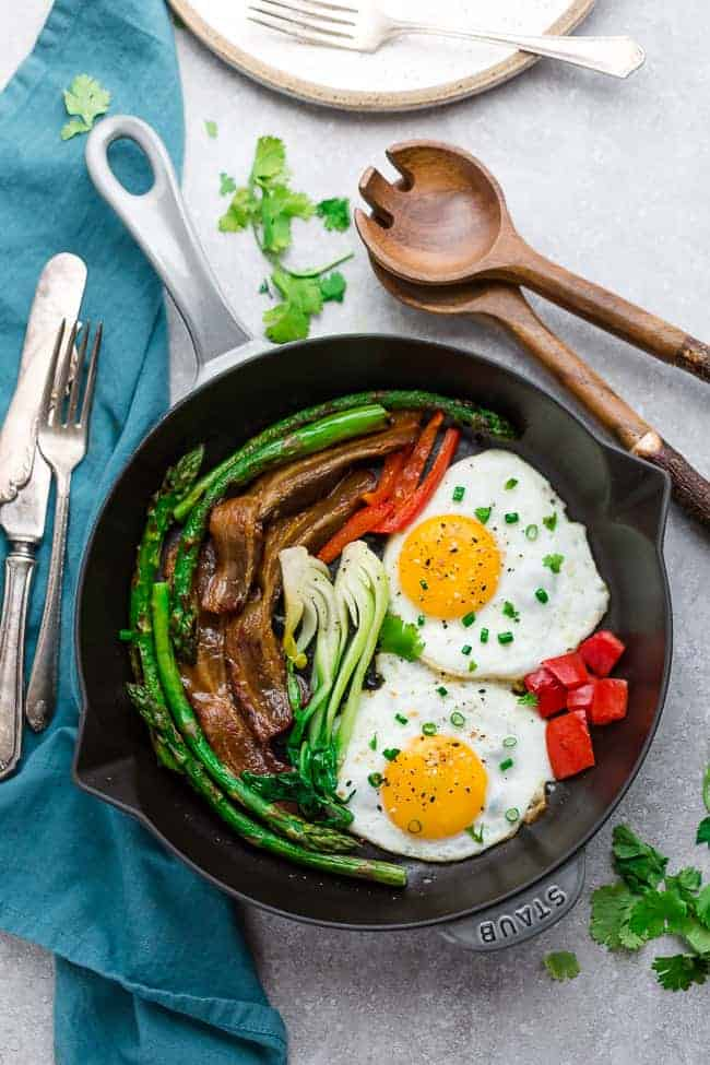 Top view of a skillet with sunny side up eggs with bacon and vegetables