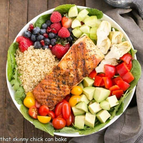 Overhead view of Superfoods Salad with a variety of fruits, vegetables, quinoa and a salmon fillet