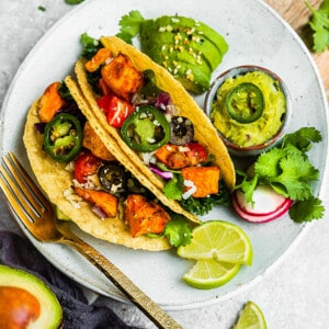 Two sweet potato tacos in grain-free taco shells on a white plate