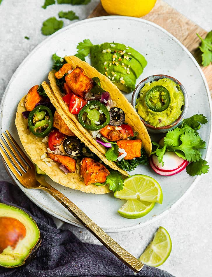 Overhead view of sweet potato tacos on a plate with avocado and guacamole