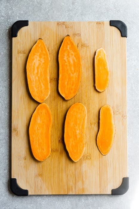 Top view of sliced sweet potatoes on wooden cutting board.