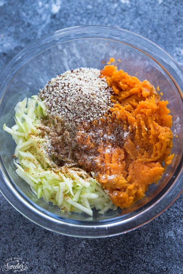 Paleo Sweet Potato Zucchini Tot ingredients in a clear glass mixing bowl.