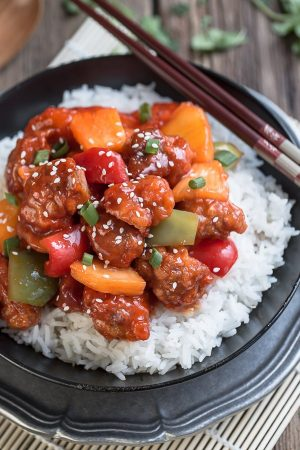 Slow Cooker Sweet & Sour Chicken on a bed of white rice on a black plate with brown chopsticks.