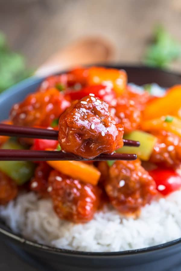 juicy piece of Sweet and Sour Chicken being held with chop sticks