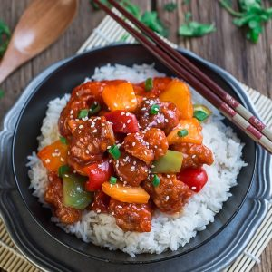 Slow Cooker Sweet and Sour Chicken over fluffy white rice in a black bowl