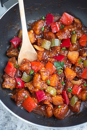 Easy and delicious Sweet and Sour Pork meal inside of a large cooking skillet with a wooden spoon.