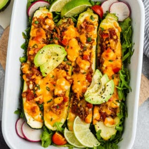 Top view of zucchini taco boats in a white casserole dish on a grey background