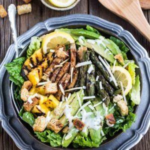 Top view of Teriyaki Chicken Caesar Salad on a black plate
