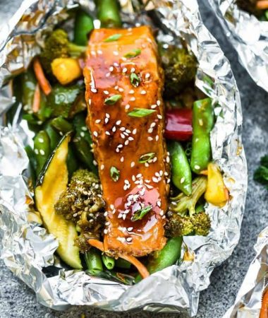 This recipe for Teriyaki Salmon Foil Packets with Vegetables is the perfect easy campfire or weekly dinner for summer. A complete meal with practically no clean up and full of your favorite sweet and savory Asian-inspired meal with perfectly tender and flaky salmon, edamame, broccoli, pineapple and red bell pepper. Make a batch for Sunday meal prep and pack it up for your lunchbox or lunch bowls. Foil packets are great for camping or busy weeknights.