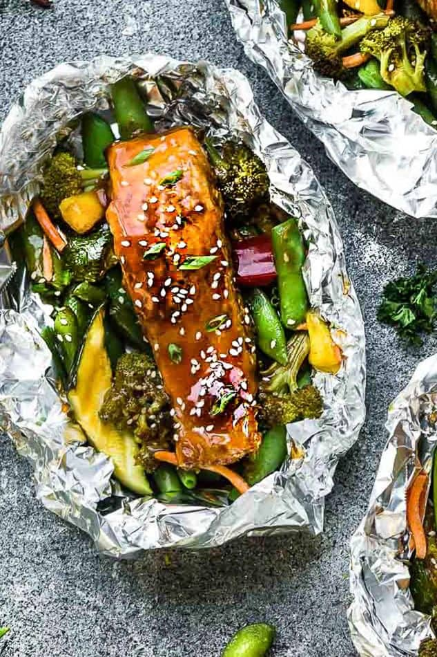 Teriyaki salmon foil recipe with fresh vegetables on grey background.