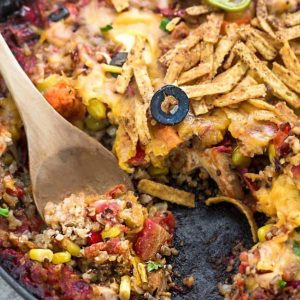 Skillet Tex Mex Casserole in a skillet with a couple scoops removed