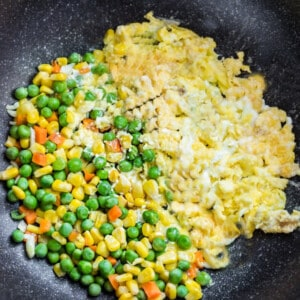 Scrambled eggs and mixed vegetables in a large black wok with white speckles