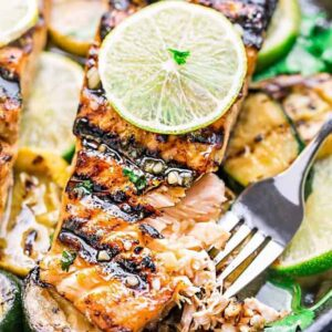 A Grilled Salmon Fillet in a Cast Iron Skillet with a Thin Slice of Lime on Top