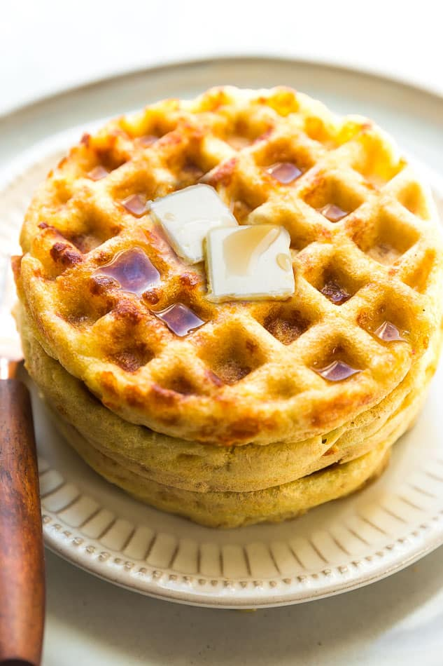 Side view of 3 stacked keto chaffles on a white plate with butter and sugar free syrup on a white plate with a fork