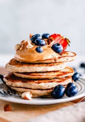 Side view of a stack of fluffy keto pancakes on a white plate with a fork and berries