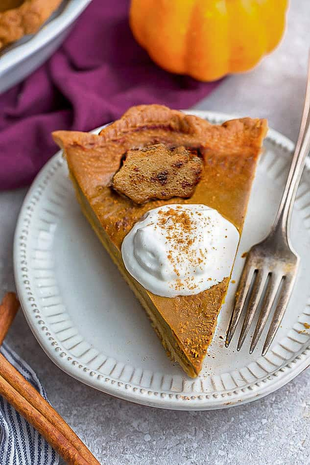 Top close-up view of keto pumpkin pie with whipped cream on a white plate with whipped coconut cream