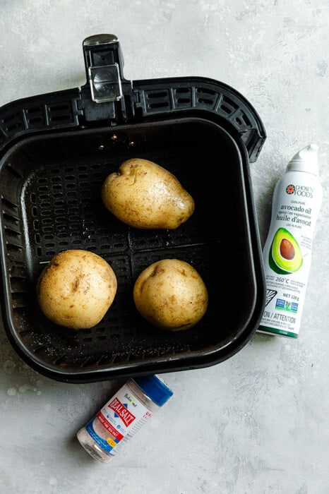 Top view of three potatoes in an air fryer basket with avocado oil spray