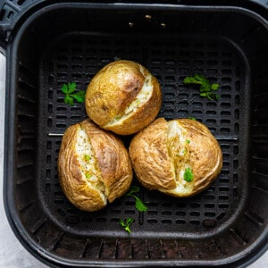 Top view of three baked potatoes with parsley in an air fryer basket